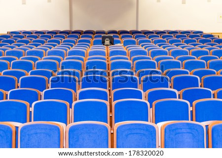 Conference hall with rows of blue seats - stock photo