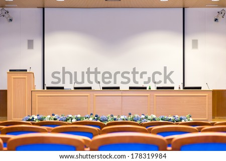 Conference hall with rows of blue seats, rostrum and screen with copy space - stock photo