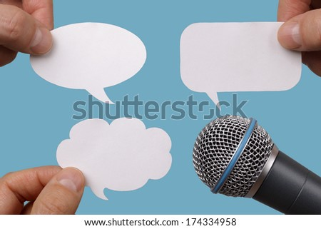 Conference, interview or social media concept with microphone and blank speech bubbles - stock photo
