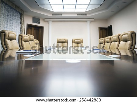 conference room with wooden table and beige leather armchairs - stock photo
