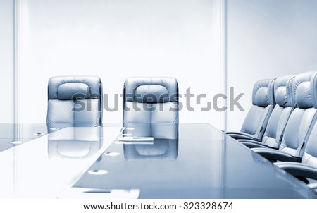 Conference room with wooden table and beige leather armchairs, blue toning - stock photo