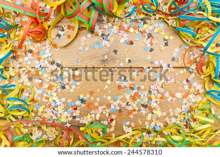 Confetti and steamer on wooden background - stock photo