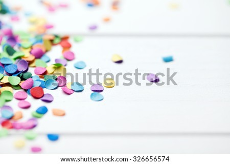 confetti on white wooden background - stock photo