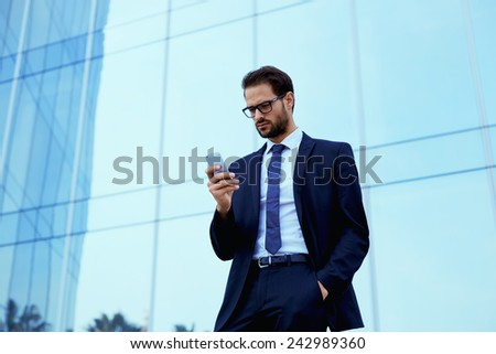 Confided businessman standing outside using a cellphone, filtered image, businessman using technology - stock photo