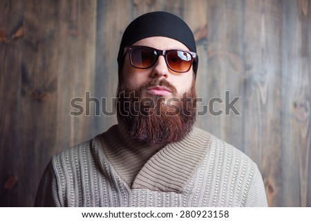 Confidence and manhood. Handsome young bearded man in sunglasses looking at camera on the wooden background