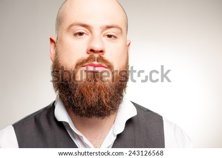 Confidence and masculinity. Handsome caucasian young bearded man looking at camera on the grey background - stock photo