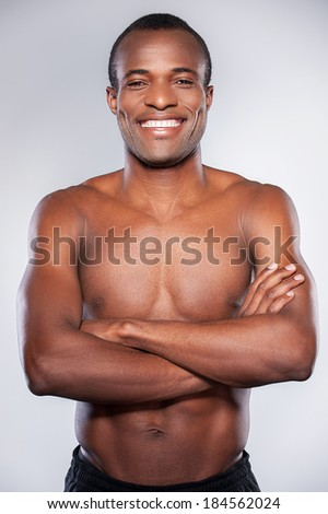 Confidence and masculinity. Young African man looking at camera and keeping arms crossed while standing isolated on grey background - stock photo