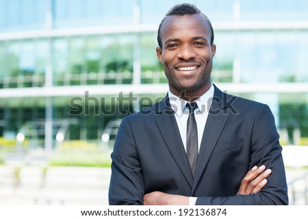 Confidence and success. Confident young African man in full suit keeping arms crossed and looking at camera while standing outdoors - stock photo