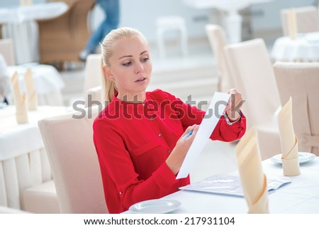 Confidence and success. Confident young businesswoman in full costume fills the paper sitting at the desk in the office - stock photo