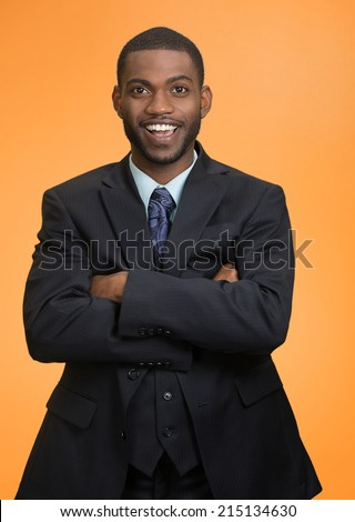 Confidence, charisma. Portrait Cheerful handsome young african american man in full suit keeping arms crossed looking at camera isolated orange  background. Human face expression emotion body language - stock photo