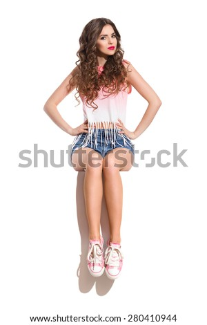 Confidence Girl Sitting. Young woman in pink sneakers, pink top and jeans shorts sitting on the top of white banner with hands on hip. Full length studio shot isolated on white. - stock photo