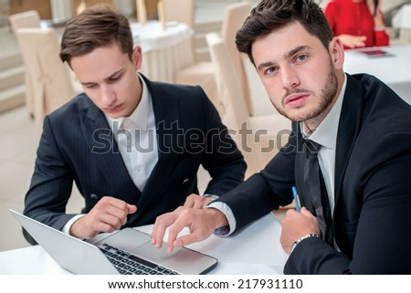 Confidence in the work. Two successful and confident businessman sitting at the table in a business office in full costume in the office and working at a laptop and looking at the camera