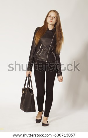 Confidence young woman with big handbag in black