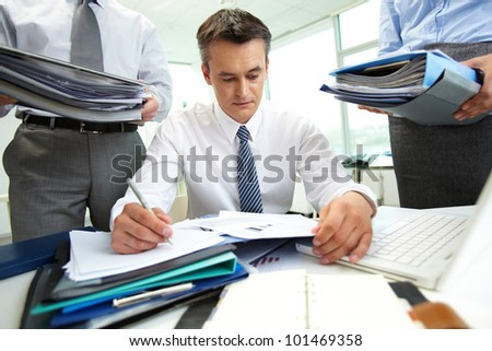 Confident accountant doing financial reports being surrounded by business partners with huge piles of documents - stock photo