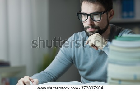 Confident adult student at the library late at night, he is sitting at desk and reading a book with hand on chin, learning and education concept - stock photo