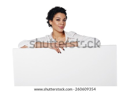 Confident african american business woman standing behind leaning at blank white banner, looking down at it, over white background - stock photo