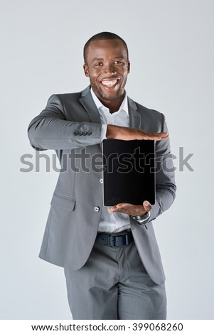Confident african black business man with touchscreen tablet device in business suit isolated in studio - stock photo