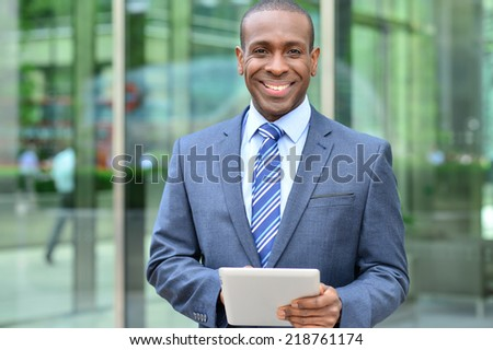 Confident african man working on digital tablet at outdoors - stock photo