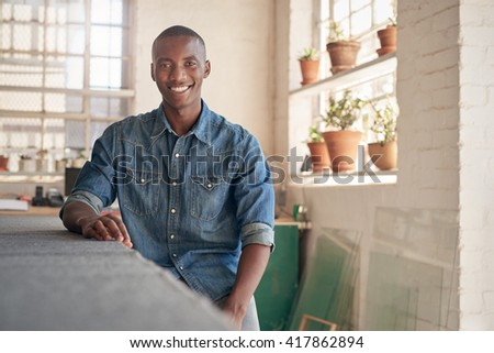 Confident African small business owner sitting inside his studio - stock photo