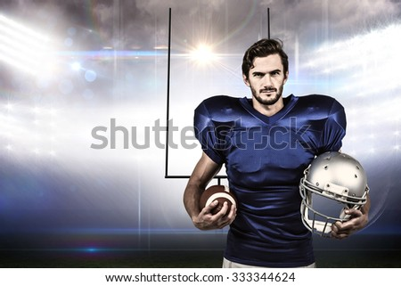 Confident american football player holding an helmet against american football arena