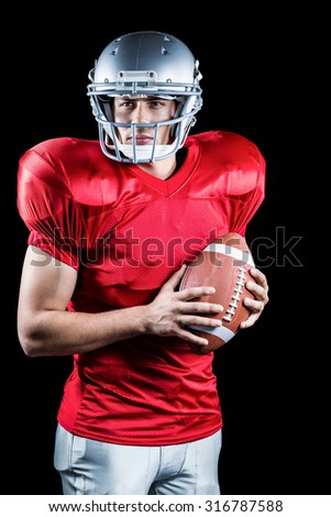 Confident American football player holding ball against black background