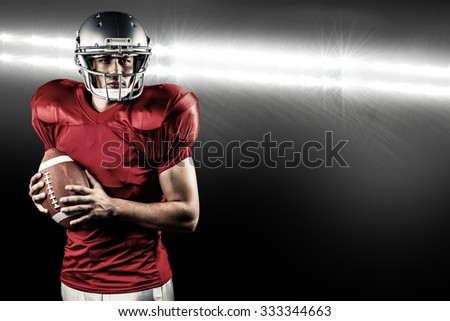 Confident American football player holding ball against spotlight