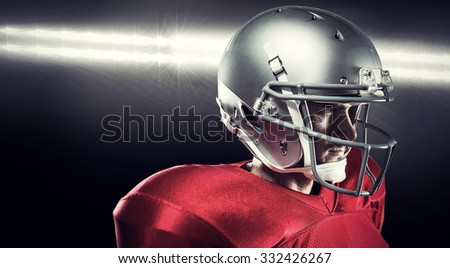 Confident American football player in red jersey looking away against spotlight
