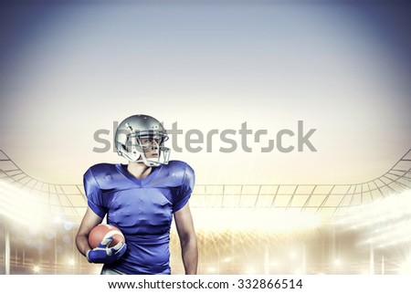Confident American football player looking away against rugby stadium