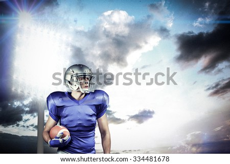 Confident American football player looking away against spotlight in sky