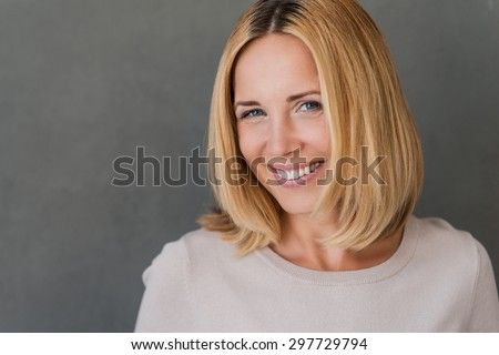 Confident and beautiful. Beautiful mature woman looking at camera and smiling while standing against grey background - stock photo