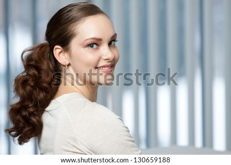 Confident and beautiful woman looking at camera over her shoulder.