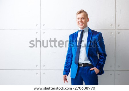 Confident and charisma. Portrait of happy young man in blue suit looking at camera while standing against white wall. - stock photo