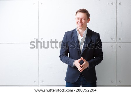 Confident and charisma. Portrait of happy young man in jacket looking at camera while standing against white wall. - stock photo