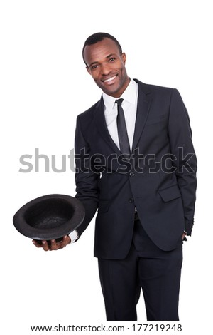 Confident and charming. Handsome young African man in full suit holding a hat in his hand and smiling while standing isolated on white background  - stock photo