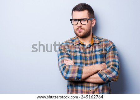 Confident and creative. Serious young man keeping arms crossed and looking at camera while standing against grey background - stock photo