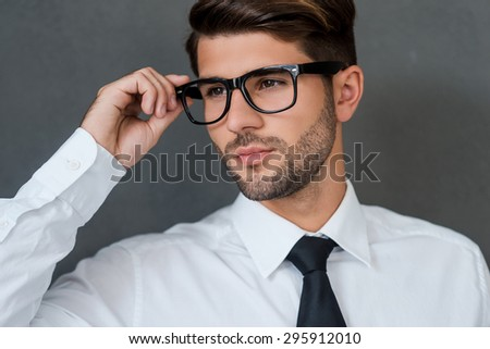 Confident and handsome. Confident young businessman adjusting his eyeglasses and looking away while standing against grey background