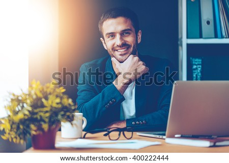 Confident and handsome. Confident young man holding hand on chin and smiling while sitting at his working place in office - stock photo