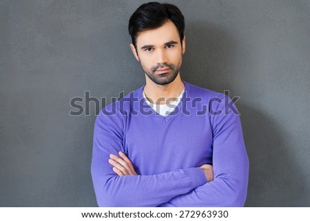 Confident and handsome. Confident young man keeping arms crossed and looking at camera while standing against grey background - stock photo