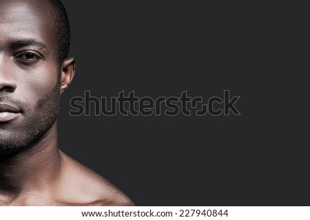 Confident and handsome. Half face of confident young African man looking at camera while standing against grey background - stock photo