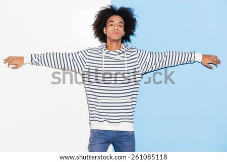 Confident and handsome. Handsome young African man stretching out his arms while standing against colorful background  - stock photo