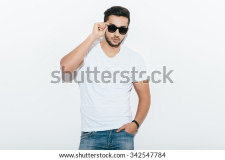 Confident and handsome. Handsome young Indian man adjusting his sunglasses and looking at camera while standing against white background - stock photo