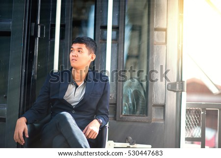 Confident and handsome. Handsome young man sitting on the wooden pallet with black wall in the background