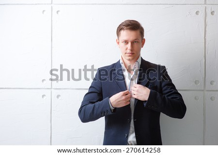 Confident and handsome. Portrait of young man in jacket looking at camera while standing against white wall. - stock photo