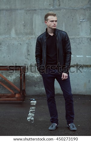 Confident and handsome young man standing near rusty metal construction over concrete wall background. Full length outdoor portrait. Hand in pocket. Street style clothes