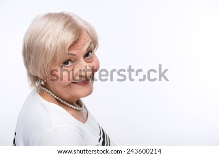 Confident and happy retired woman. Closeup shot of elderly woman looking over shoulder and smiling at camera standing against white background - stock photo