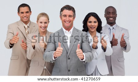 Confident and smiling business team with thumbs up - stock photo