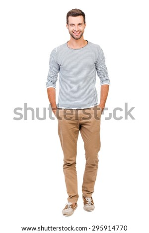 Confident and stylish. Full length of cheerful young man holding hands in pockets and looking at camera while standing against white background - stock photo