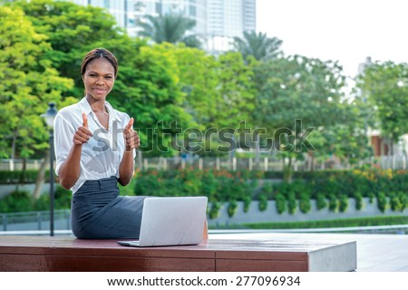 Confident and successful business in Dubai. Smiling African businesswoman businessman sitting in the street and working at a laptop in Dubai downtown showing thumbs up - stock photo