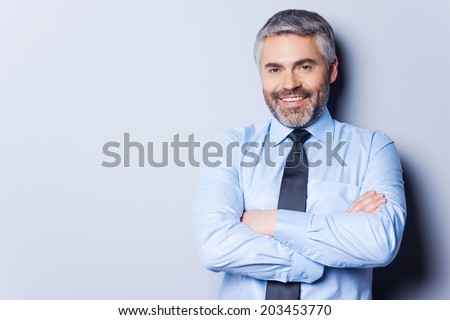 Confident and successful. Cheerful mature man in shirt and tie looking at camera and keeping arms crossed while standing against grey background - stock photo