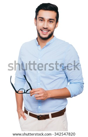 Confident and successful. Confident young Indian man carrying his eyeglasses and smiling while standing against white background - stock photo
